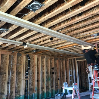 Guys installing what will be decorative open beams in the kitchen